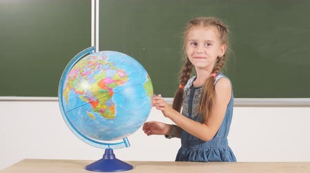 экономить : Charming little girl with globe, looking at camera , standing on chalkboard background