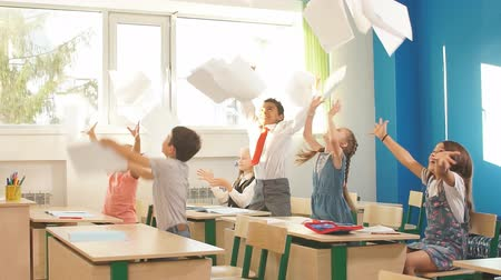 ура : Group of school kids have fun in class and throwing paper in air Стоковые видеозаписи
