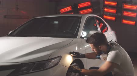 detailing : Man checks result of polishing of car with a flashlight
