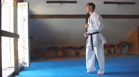 tanítvány : Caucasian Man in white kimono with black belt training karate in gym