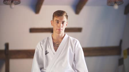 oturur : Karate do man in kimono sits on knees on floor in martial arts gym