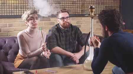 экипаж : Attractive young men and woman are talking while smoking the hookah. Entertainment and conversation concept Стоковые видеозаписи