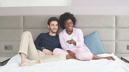 giymek : Happy interracial couple in home wear, relaxing in bed holding remote control and watching television
