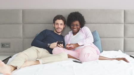 darkskinned : Young wife and husband relaxing on bed during their day-off.