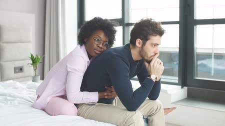 empregos : Mixed raced couple sitting in bedroom with gloomy expression, sexual related problems. Thoughtful caucasian man having stress while her African girlfriend sitting behind and touching his shoulder