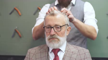 cortiça : Hairdresser s work for a handsome respectable old-aged bearded man at the barber shop. He is doing styling with the electric shaver.