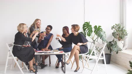 dark skinned : Excited african and caucasian business ladies celebrate with champagne at office meeting motivated by victory, achievement or good work result.