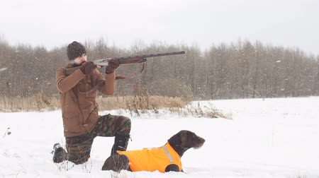 game hunting : young man is aiming at a bird while dog is waiting for a shot. killing animals