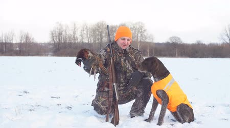 forgatás : Positive hunter with dogs during the rest on winter hunting. hobby, interest