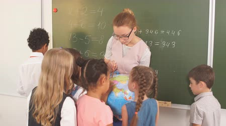 listener : groupof cute schoolchildren and teacher looking at globe in classroom