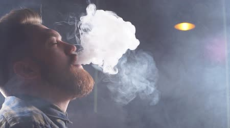 inebriated : Young relaxed man with red beard is inebriated by tobacco. Slow motion Stock Footage