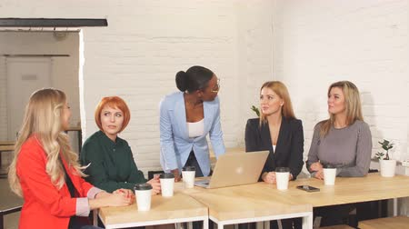 diferença : Happy African business woman, group leader celebrating success with female members of her team, being overjoyed, clapping hands with the others at meeting. Stock Footage