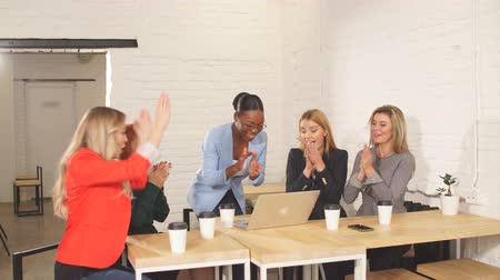 african decent : Cheerful young dark-skinned African female Chief giving high five with her caucasian co-workers, looking at each other with happy smiles, cheering and celebrating successful teamwork at meeting. Stock Footage