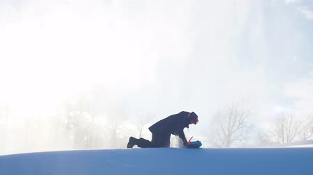 ski boots : Snowboarder prepares for freeride session.sporty man sitting on the snow and preparing the tool. athlete fixing the snowboard