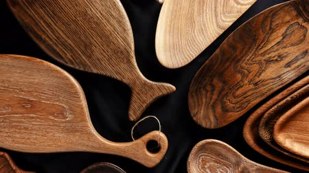 kullanılmayan : unused brand new brown handmade wooden kitchen utensil, made from different wood species, dish plate and cutting board on black background Stok Video