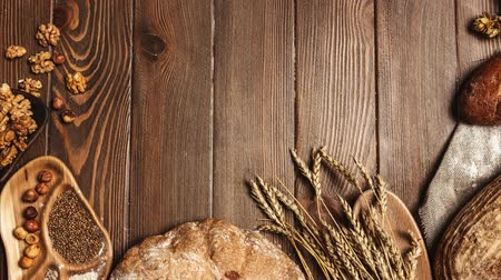 mistura : Various bread selection flat-lay. Top view of rye, wheat and multigrain rustic bread loaves over dark wooden vertical planks background with a blank copyspace for text in the middle of circle Stock Footage
