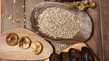 owies : Whole grain, whole loaf and sliced pieces of multigrain bread contains whole grains ( poppy, millet, flaxseed, pumpkin seeds, and sunflower seeds) isolated on dark wooden table . Wideo