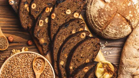 kasza jaglana : Whole grain, whole loaf and sliced pieces of multigrain bread contains whole grains ( poppy, millet, flaxseed, pumpkin seeds, and sunflower seeds) isolated on dark wooden table . Wideo