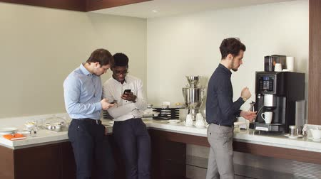 trabalho em equipe : Handsome guy making coffee while his colleagues are watching something on smartphones