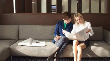 занятость : Two female friends reading newspaper news during sitting on a, girl pointing to newspaper and talking about something to her curious colleague. Mass media