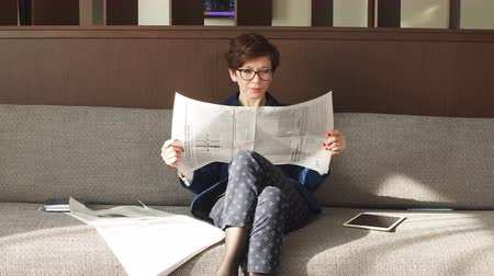 holding newspaper : Positive business woman holding newspaper and resting after work, free time, hobby, lifestyle
