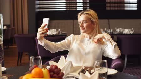 blúz : Stylish young elegant woman sitting at cafe and taking selfie with her smart phone, free time, girl taking picture to herself while having a dinner