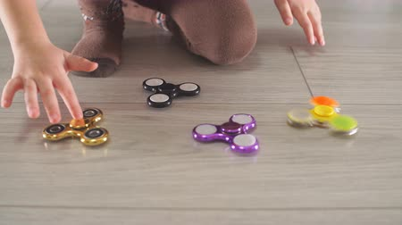 camera rotation : Little child playing with modern popular hand toy spinner. Boy playing rotating golden anti stress spinners with one hand. Stock Footage