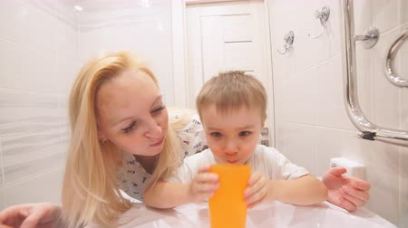 persons : Mom and son brushing their teeth together. Mom teaches her son to brush his teeth