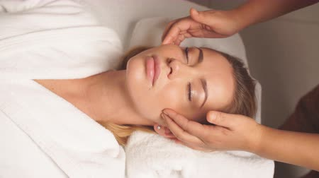 massagista : Gorgeous woman enjoys spa treatment in clinic. Girl takes care of her face