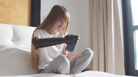 łokieć : Girl checking her robotic mechanical arm indoors.