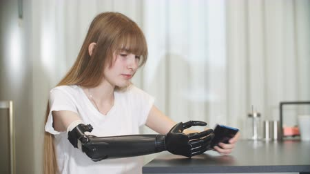 rehabilitasyon : Disabled girl checking her metal prosthetic arm