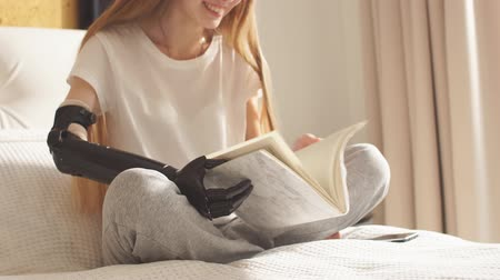 amputee : Disabled girl enjoys reading a book in the bedroom. Education, learning