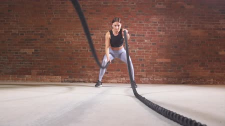 concentrando : Hard work of female crossfit instructor proves that training ropes are a very dynamic workout. Slow motion