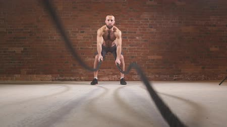squatting : Handsome muscular bare chested gym man is doing battle rope exercise while working out at cross-fit training. Slow motion
