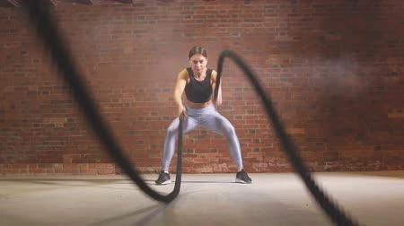 squatting : Hard work of female crossfit instructor proves that training ropes are a very dynamic workout. Slow motion
