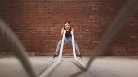 squatting : Caucasian fit woman dressed in sports outfit exercising with battle ropes at gym. Slow motion Stock Footage