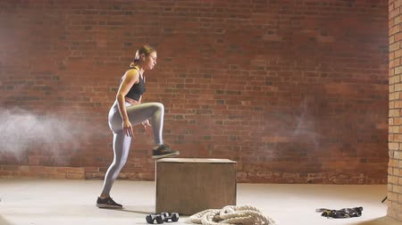 odaklanma : Young strong woman with perfect fitness body in sportswear doing set of box jumps at the gym. Girl jumping into wooden boxes in a training. Crossfit workout. Slow motion