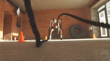 cordas : Afro american bodybuilder with battle rope in cross-fit training centre.