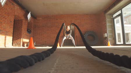 squatting : Caucasian fit woman dressed in sports outfit exercising with battle ropes at gym.