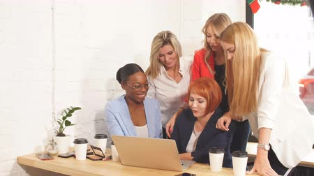 stage : Group of designers working on a project as a team, diverse women gathered together near laptop of red-haired female colleague.