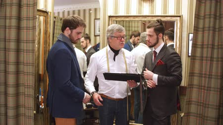comparar : Two handsome and successful businessman trying on a custom made stylish suit at tailors shop. Dressmaking and Tailoring establishment concept