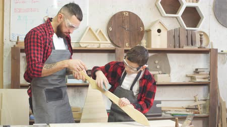 dýka : Little male woodworker creating his dream and his Dad is helping him. Close-up of young male carpenter examines with his son smoothness of DIY wooden sword to work with wood in his workshop