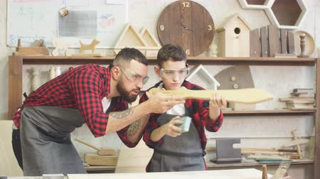 dýka : Fatherhood, hobby, carpentry, woodwork and people concept - Father and little son wearing protective glasses testing hand-made wood sword smooth surface at workshop