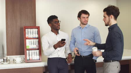 африканского происхождения : Successful young businessmen are having a conversation during the coffee break in office.