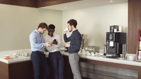 etnia africano : Black-haired elegant man with cup of coffee giving advice to his clients. Consultation in the informal atmosphere Stock Footage