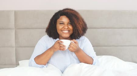 newspaper cover : Attractive girl gets pleasure from drinking hot tea in morning, morning beverage. Woman adores tea Stock Footage