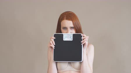 eredmények : Anorexic girl with a sad face holds the scales and looks at camera, on a gray background. Stock mozgókép