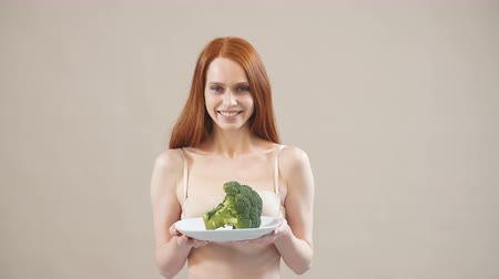 сантиметр : Joyful skinny girl keeps broccoli in a plate, obsessed with malnutrition, afraid of excess weight, anorexia