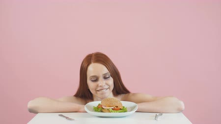 сантиметр : Happy anorexic girl struggles with the temptation to eat a Burger.