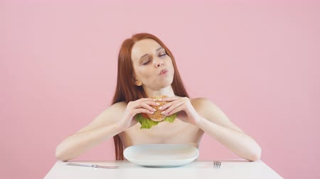 modelagem : Happy skinny girl breaks the diet and eats a Burger. Violation of diet. Anorexia. Vídeos